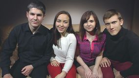 Two guys and two are girls sitting on the couch. Two guys and two girls are sitting on the couch and looking at the camera, gradually approaching stock footage