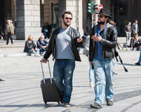 Two guys are walking through the streets of Genova, Italy and looking around, talking to each other. Stock Photo