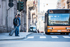 Two friends are crossing the street in busy area. Two guys are walking through the streets of Genova, Italy and looking around, talking to each other. Touristic Royalty Free Stock Photos