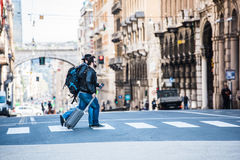 Two friends are crossing the street in busy area. Two guys are walking through the streets of Genova, Italy and looking around, talking to each other. Touristic Royalty Free Stock Photography