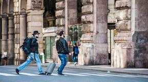Two friends are crossing the street in busy area. Two guys are walking through the streets of Genova, Italy and looking around, talking to each other. Touristic Royalty Free Stock Photo
