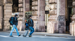 Two friends are crossing the street in busy area. Two guys are walking through the streets of Genova, Italy and looking around, talking to each other. Touristic Stock Photos