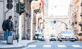 Two friends are crossing the street in busy area. Two guys are walking through the streets of Genova, Italy and looking around, talking to each other. Touristic Stock Image