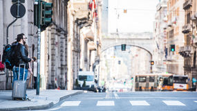 Two friends are crossing the street in busy area. Two guys are walking through the streets of Genova, Italy and looking around, talking to each other. Touristic Stock Images