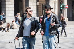 Two guys are walking through the streets of Genova, Italy and looking around, talking to each other. Stock Photos