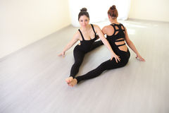 Two gymnast women doing stretching exercise in white interior. Practicing yoga in the gym. two sporty women practice yoga in pair, Sports women doing stretching Stock Image