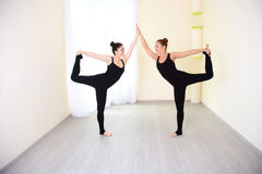 Two gymnastwomen, dressed in sportswear practicing yoga. Two sporty gymnast women working out in  gym, doing yoga exercise. Athletes dressed in a stylish Stock Photos