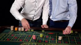 Two gyus with winning player getting his chips. Black. Two gyus with winning player getting his chips, roulette, a white shirt, one winner, victory, fortune stock video