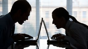 Two hackers. Profiles of man and woman typing on laptops in office Royalty Free Stock Photo