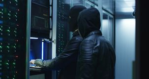 Two hackers beginning an attack on servers. Medium shot of two hackers beginning an attack on servers with laptops in corporate data center stock video footage