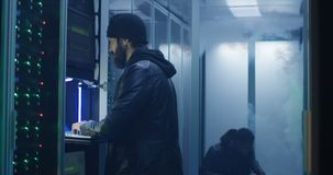 Two hackers finishing hack and escaping a smoke-filled room. Medium, slow motion shot of a two hackers finishing hack and escaping a spark and smoke-filled stock video footage