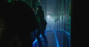 Two hackers finishing hack and escaping a smoke-filled room. Wide, slow motion shot of a two hackers finishing hack and escaping a spark and smoke-filled stock footage