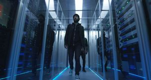 Two hackers walking through rows of servers. Wide shot of a two hackers walking through corporate data center with rows of working rack servers stock video footage