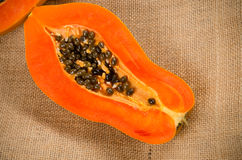 Two haft of fresh papaya with sackbag. Haft of fresh papaya with sackbag on wooden background Stock Photography