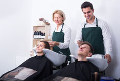 Two hairdressers working with clients Royalty Free Stock Image