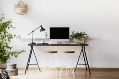 Two hairpin stools placed by black desk with metal lamp, fresh plant and mockup monitor in real photo of white living room interio. R with empty wall stock images