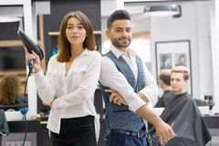 Two hairstylers posing standing in modern spacy beaty salon. stock photo