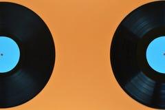 Two half black vinyl record on orange background Royalty Free Stock Images