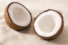 Two half coconut. Lying in sand Royalty Free Stock Images
