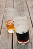 Two half filled glasses of light and dark beer. On a wooden table Royalty Free Stock Images