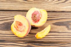 Two half of fresh ripe peach with peach stone and one slice of peach. On rustic old wooden planks stock image