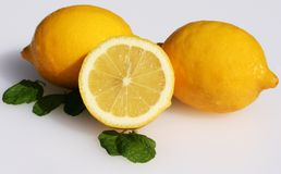 Two and half lemons. Three Lemons, one of which is cut in half resting on leaves royalty free stock photography