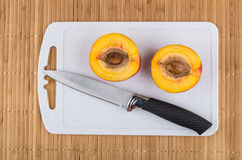 Two half of nectarine and knife on cutting board Stock Images