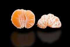 Two half peeled mandarin on pure black background. Royalty Free Stock Images