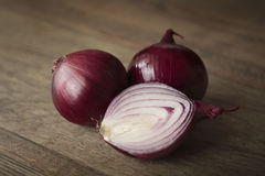 Two and a half. Two red onions and one half on wooden background Royalty Free Stock Image