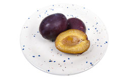 Two and a half red plum on a ceramic plate. Two whole and one half red plum on a handmade ceramic plate, decorated with colored dots Royalty Free Stock Photos