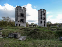 Two half-ruined towers in the wasteland. Two Unfinished high-rise buildings against the blue sky on a cloudy day Stock Photo