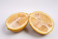 Two half yellow fresh lemon in rough skin, perpendicular to each other over the white background. Two half yellow fresh lemon in rough skin, perpendicular to Royalty Free Stock Photos