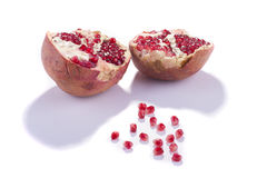 Pomegranate. Two halfs of pomegranat with little shots isolated on white background royalty free stock images