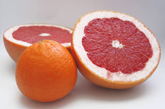 Two halfs of red grape fruit and an orange Royalty Free Stock Image