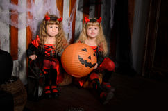 Two halloween devils girls with pumpkins. Two halloween devils girls, little sisters twins, with horns in costumes in black and red with pumpkins indoors stock photography