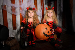 Two halloween devils girls with pumpkins. Two halloween devils girls, little sisters twins, with horns in costumes in black and red with pumpkins indoors stock images