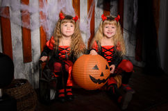 Two halloween devils girls with pumpkins. Two halloween devils girls, little sisters twins, with horns in costumes in black and red with pumpkins indoors royalty free stock photo