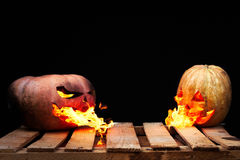 Two Halloween pumpkins on the boards against each other spew fla. Mes fire on a black background Stock Photo