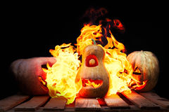 Two Halloween pumpkins on the boards against each other spew fla. Mes fire on the third pumpkin on a black background Stock Image
