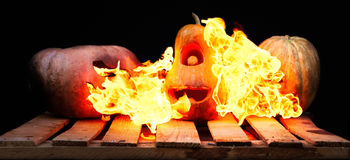Two Halloween pumpkins on the boards against each other spew fla. Mes fire on the third pumpkin on a black background Royalty Free Stock Photo