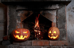 Two Halloween pumpkins at the fireplace with fire. Two Halloween pumpkins glowing at the fireplace with fire Stock Images
