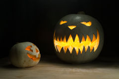 Two halloween pumpkins. Funny and spooky on wood table with dark on background Stock Photography