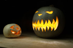 Two halloween pumpkins funny and spooky on wood table Stock Images