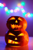 Two Halloween pumpkins head jack lantern with colorful lights on background Stock Photos