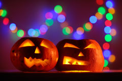 Two Halloween pumpkins head jack lantern with colorful lights on background Royalty Free Stock Image