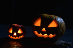 Two halloween pumpkins jack faces in the dark. With moonlight on hardwood Royalty Free Stock Photos