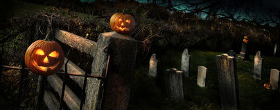 Two Halloween pumpkins sitting on fence Stock Photography
