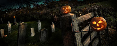 Two Halloween pumpkins sitting on fence Stock Photos