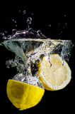 Two halved lemons splash into water Royalty Free Stock Images