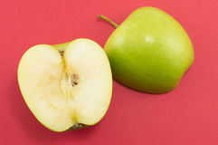 Two halves of an apple on red background Royalty Free Stock Images